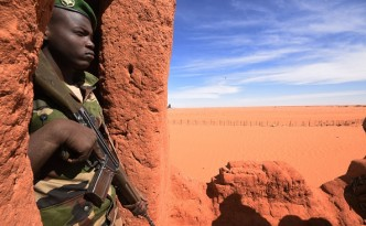 A Nigerian soldier stands guard in Madama near the border with Lybia on January 1, 2015. French Defence Minister Jean-Yves Le Drian paid a surprise visit to northern Niger on January 1, to visit a base being built to combat the growing flow of weapons and jihadists from neighbouring Libya. Le Drian travelled from Chad to Madama, a desert outpost about 100 kilometres from Libya, where he saw in the New Year with troops at a French base. Madama is situated on the route used by jihadists and arms smugglers in southern Libya to reach northern Mali and Niger.   AFP PHOTO / DOMINIQUE FAGET        (Photo credit should read DOMINIQUE FAGET/AFP/Getty Images)